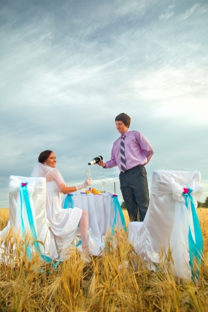 field glass: Bride and groom next to wedding table on the wheat field Stock Photo
