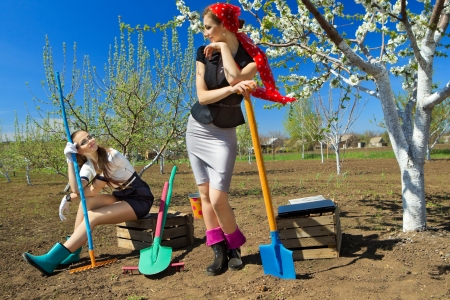 women in boots: Portrait of two young females with rakes and spade on garden