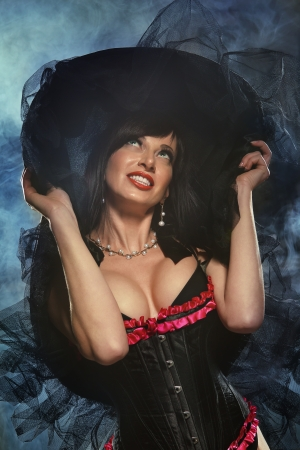 erotic fantasy: Sexy witch dressed up in black corset covered in smoke