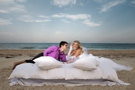 pareja en la cama: Hermosa joven pareja descansando en la cama en la ma�ana en la playa
