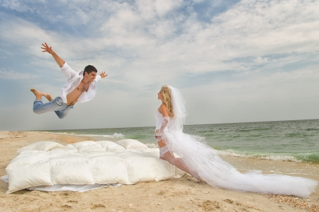 Happy Groom flying on bed to his bride on the beach