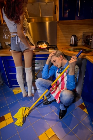 mopping: Concept Man resting on the kitchen floor and looking at his girlfriend Stock Photo