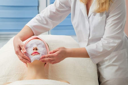 Young beautiful girl receiving facial mask in spa beauty salon photo