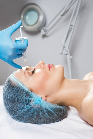 augmentation: Young woman receiving a botox injection in her front Stock Photo