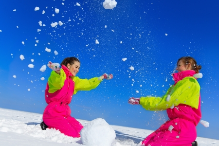 Two young woman throwing snow on blue sky and sculpting snowman in street in wintertime Standard-Bild
