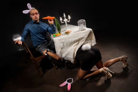Lovely woman in rabbit costume is seducing her boyfriend bunny under table