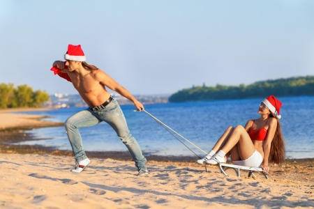 Santa pulling Sexy Santa girl on a sled at the beach.(concept: Tropical winter fun) photo