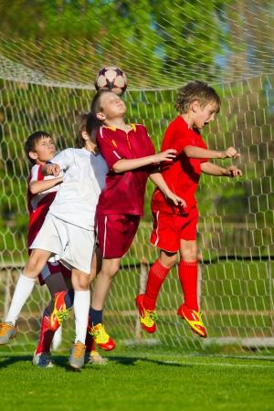 playing football: Ni�os jugando al f�tbol en el campo de deportes junto a meta Foto de archivo
