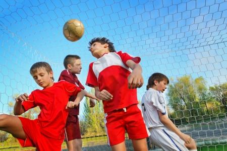 cerillos: Ni�os jugando al f�tbol en el campo de deportes junto a meta Foto de archivo