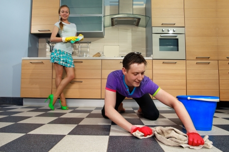 Young man cleaning floor and looking at her girlfriend Standard-Bild