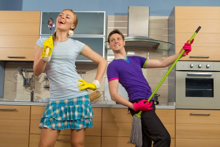 charwoman: Modern kitchen - woman pretend to sing song with ladle and smiling young man cleaning the floor at home and play like guitar with  mop