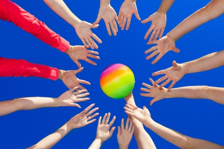Several hands reaching out together in a circle for volley ball against blue sky photo