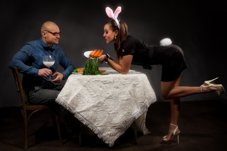 Lovely woman in rabbit costume is  feeding her boyfriend bunny photo