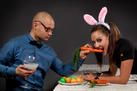 Lovely man in rabbit costume is feeding his girlfriend bunny