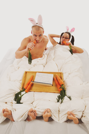 Lovely couple in rabbit costumes lying on bed and watching laptop photo