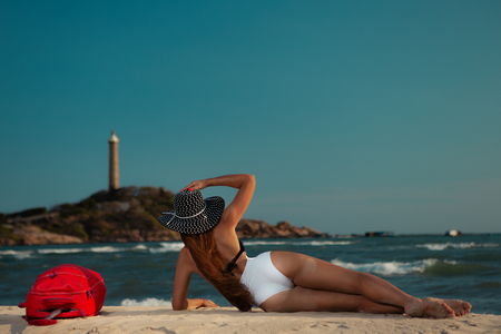 Woman on tropical beach  hat with large red suitcase