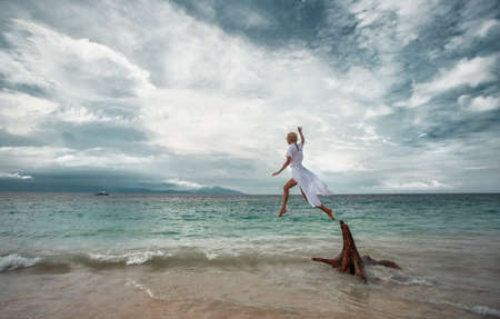 Woman is jumping at the beach Imagens