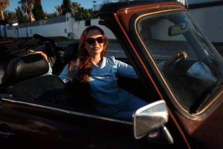 Beautiful young woman sits inside convertible car