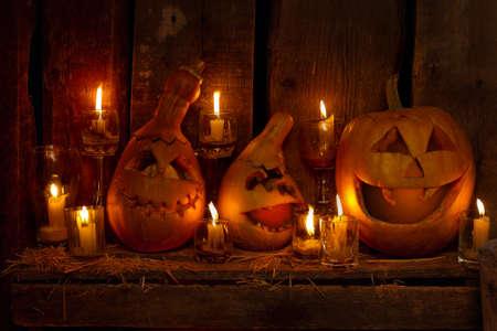 Scary Jack O 'Lantern Halloween pumpkins on a wooden background