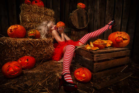 Beautiful sexy woman with Halloween pumpkins against wooden background Standard-Bild - 156623331