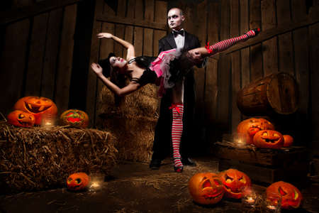 Portrait of a man and sexy woman vampires with Halloween pumpkins against wooden background