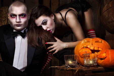 Portrait of a man and woman vampires with Halloween pumpkins against wooden background
