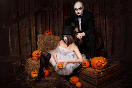 Portrait of a man and sexy woman vampires with Halloween pumpkins against wooden background Standard-Bild - 156623336