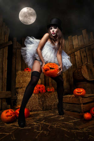 Beautiful woman with Halloween pumpkins against wooden background