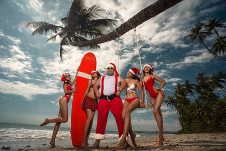 Christmas Santa Claus resting at ocean sandy tropical beach with beautiful sexy girls