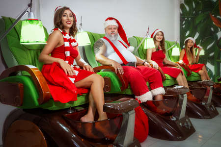 Santa Claus is sitting in a spa salon with his beautiful female helpers. Manicure and pedicure salon interior.