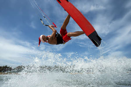 Santa Claus professional kitesurfer rides sea waves and flying over water