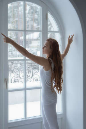 Beautiful girl is doing everyday exercises next to big window Standard-Bild