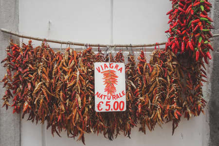 Hanging bundles of red hot peppers at a local farmers market, Spain Stock Photo