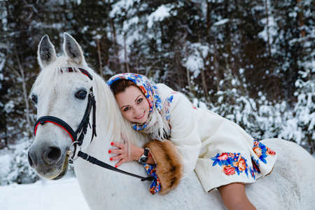 Pretty woman in traditional clothes is riding her horse (focus on the horses face) Standard-Bild