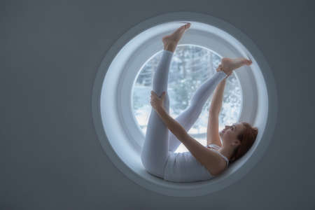 Beautiful girl in white sportswear lies in a round window