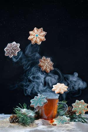 Cup of tea with steam and star shaped gingerbread cookies