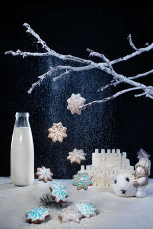 Milk and gingerbread cookies in star shape on snowy background with snowman and falling snow from branches