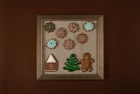Frame with Christmas ginger cookies on brown wall