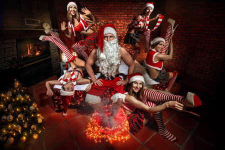 Portrait of Santa Claus sitting on a bed and steaming his legs, surrounded by sexy girls in Santa hats. Standard-Bild