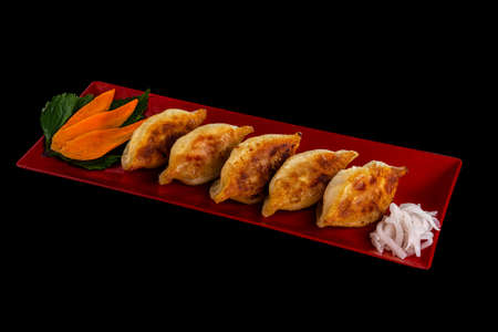 Gyoza or dumplings snack with carrot and radish on black background Standard-Bild