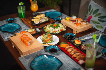 Side view of a table with Japanese cuisine: Flower dish set and inari sushi set in focus against various side dishes.