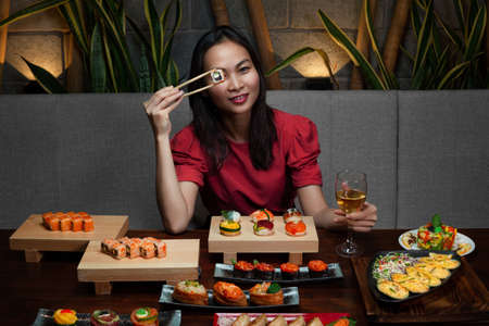 Portrait of woman holding chopsticks with nishin nigiri opposite her eye and enjoying various Japanese side dishes: Philadelphia, Tuna uramaki and Flower sushi set