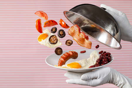 Waiter is opening plate with levitating sausages, bacon, beans, scrambled eggs, tomatoes and mushrooms on vintage pink striped background