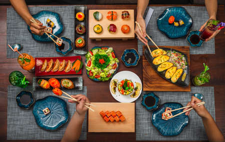 Top view of a table with Japanese cuisine: Flower dish set and inari sushi set with various side dishes.