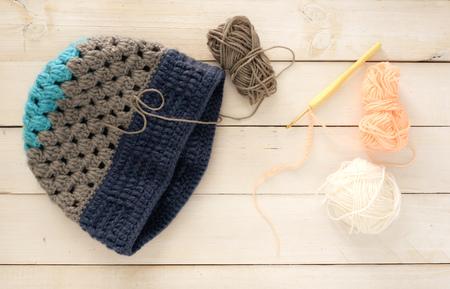 毛糸のボールとかぎ針編みの帽子、2つのウールの帽子とかぎ針編みの作業木製のテーブル、冬のコンセプトのトップビュー