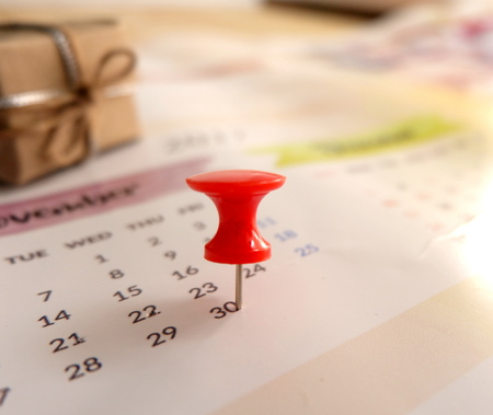 Calendar with red pin for planning with gift box