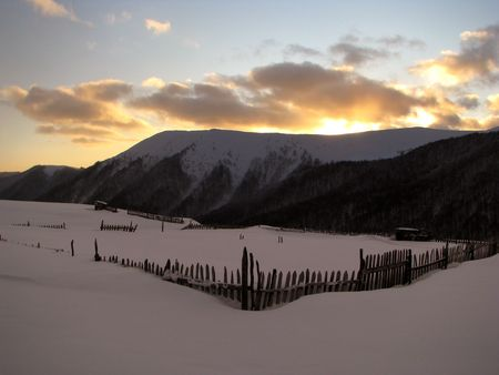 Winter sundown. Winter sunset in the mountainous village. Scenic twilight   Stock Photo