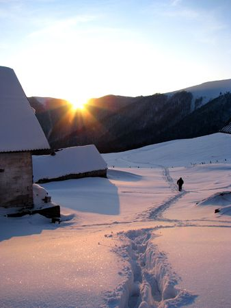 Winter evening in the mountainous village. Sunset in the mountainous village. Winter landscape.
