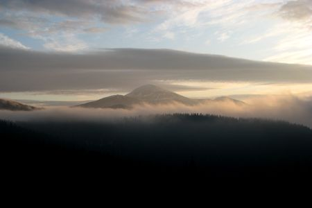 Morning in the mountains. Cloudy dawn in the mountains. Clod-drift over the ridge.