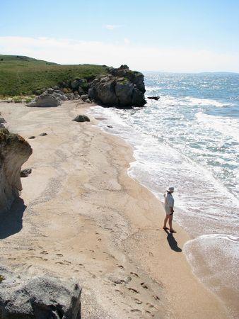 Women on the coast. Scenic beach and women near the sea. Marine. Holiday season.